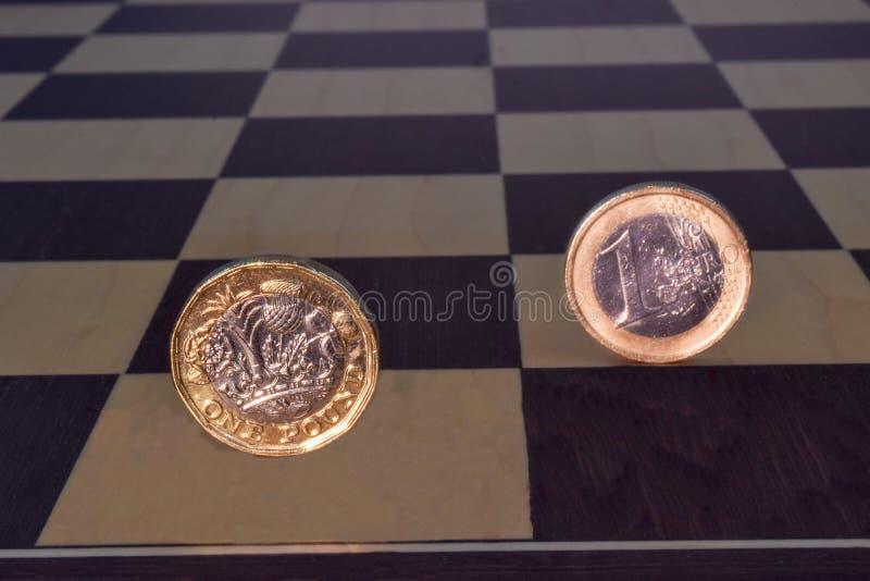 Pund- och euromynt på ett schackbräde royaltyfri foto