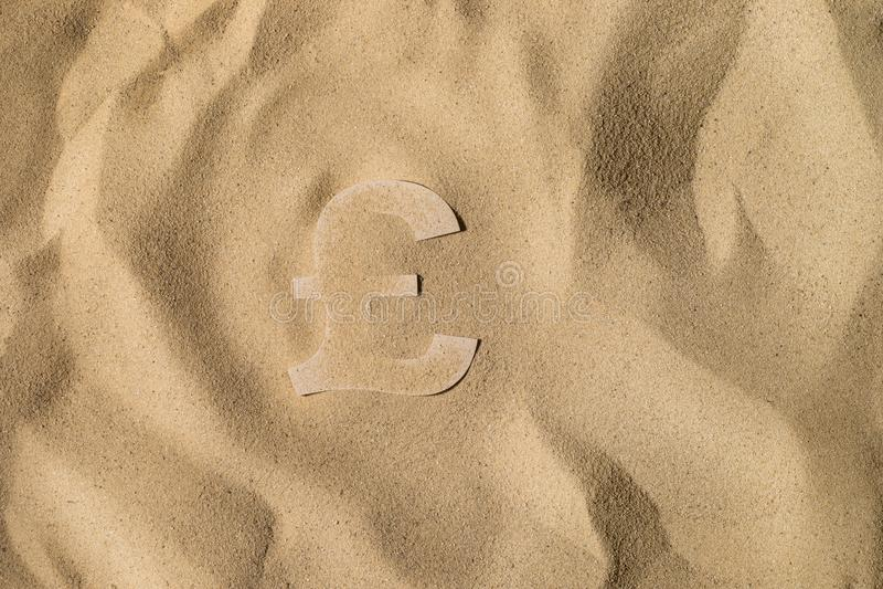 Pundsymbol under sanden arkivfoton