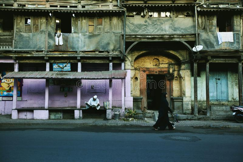 PUNE, INDIA, July 2012, Man reading the newspaper at old building or wadas royalty free stock images