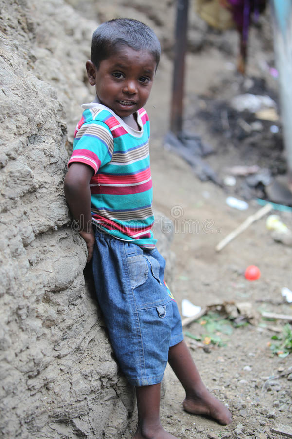 Pune, India - July 16, 2015: A poor Indian boy standing at a con royalty free stock image