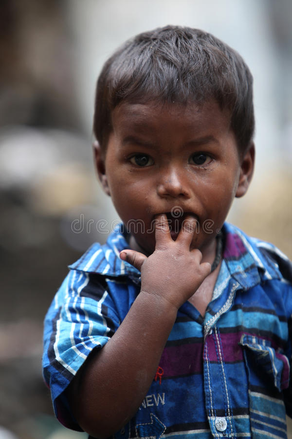 Pune, India - July 16, 2015: A portrait of a poor Indian boy put royalty free stock image