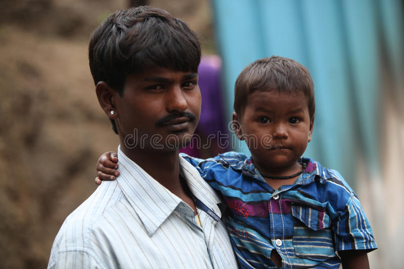 Pune Indien - Juli 16, 2015: Lite pojke med hans fattiga fader w royaltyfria bilder