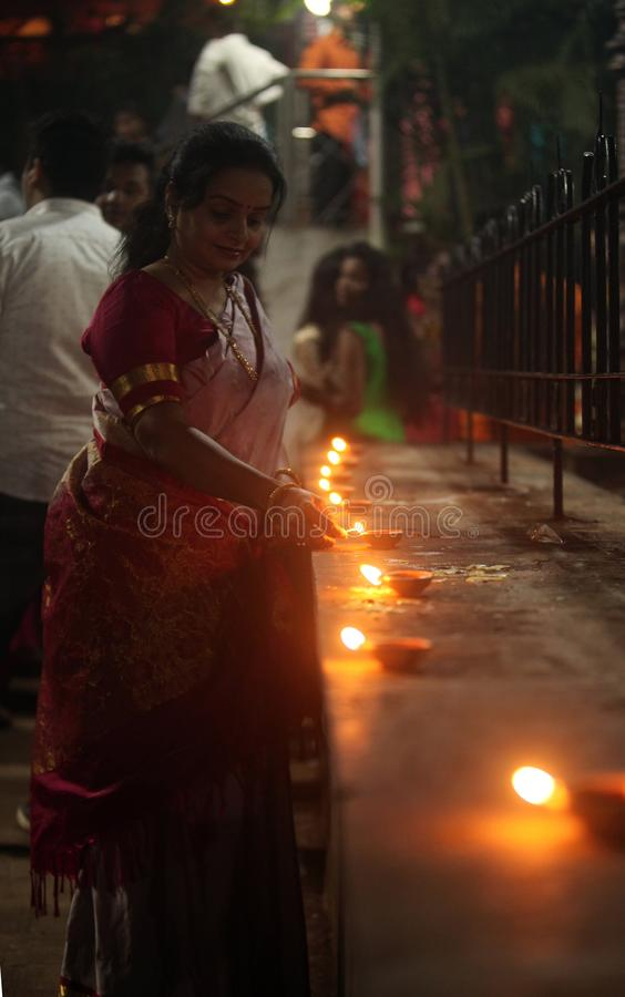 Pune, Indien - November 2018: Eine Frau leuchtet Lampe vor stockfotografie