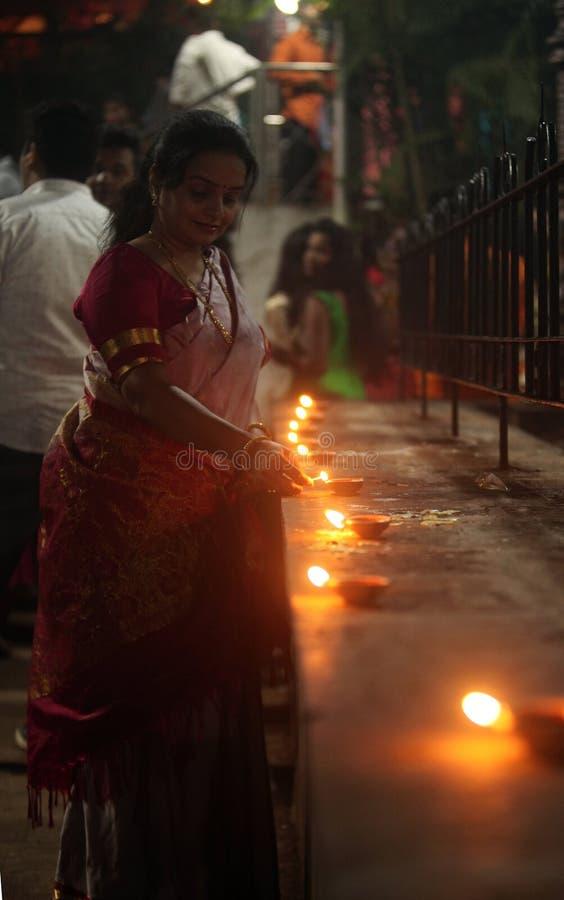 Pune, la India - noviembre de 2018: Una mujer enciende para arriba la lámpara delante de fotografía de archivo