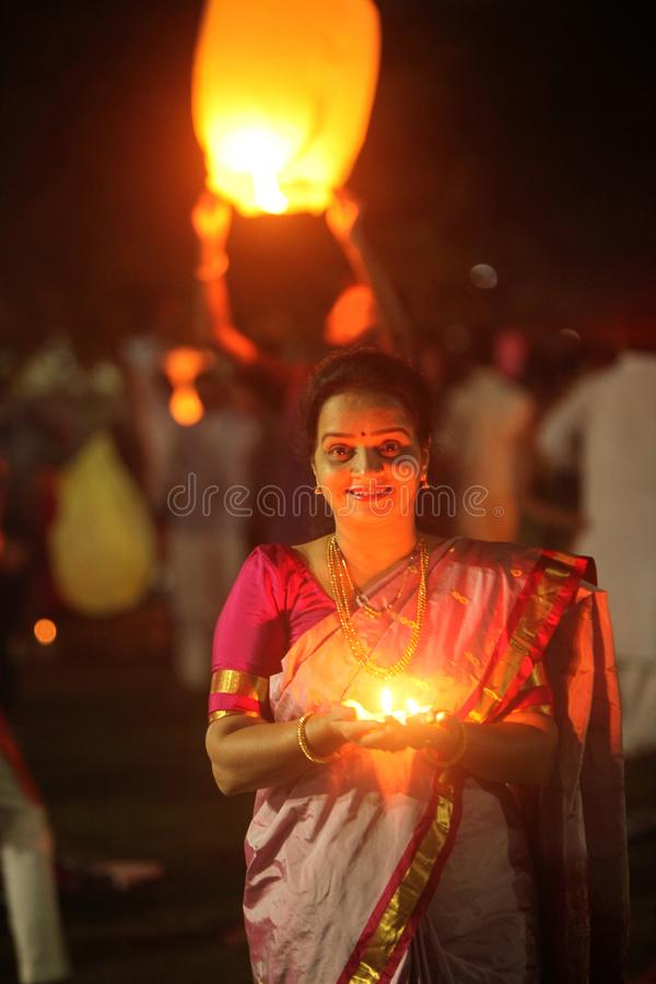 Pune, la India - noviembre de 2018: Una mujer enciende para arriba una lámpara durante un p imagen de archivo libre de regalías