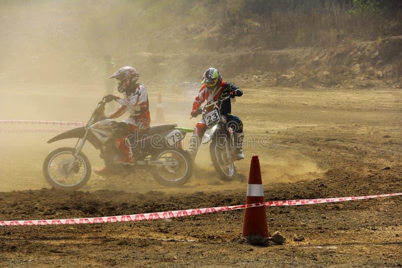 PUNE MAHARASHTRAEN, INDIEN, Februari 2018, motorcykeltävlingsförare konkurrerar med de under loppet för smutskorsmotorcykeln arkivfoton