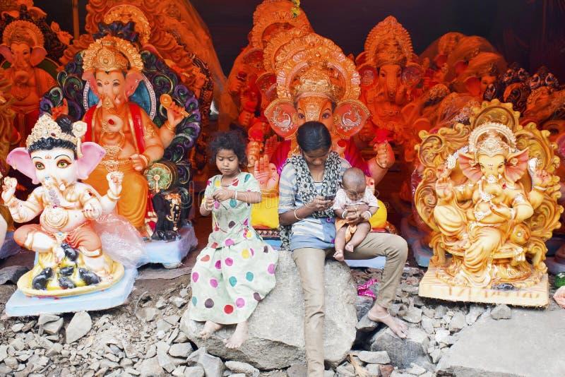PUNE, MAHARSHTRA, septembre 2015, des enfants à la rue font des emplettes avec des idoles de Ganpati pendant le festival de Ganes photos libres de droits