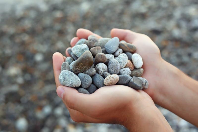 Punhado das pedras nas mãos, de encontro às pedras foto de stock royalty free
