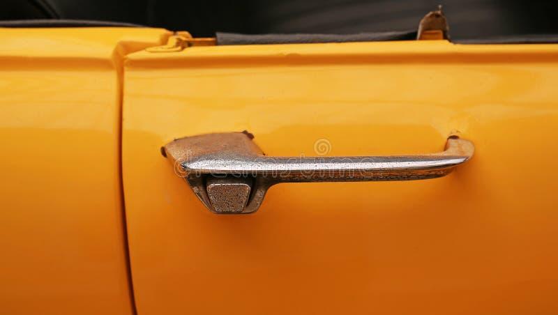 Punho cromado close-up do carro clássico amarelo do vintage foto de stock