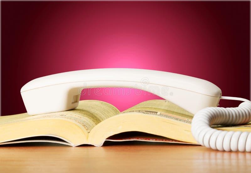 Punho da lista telefônica e do telefone na tabela de madeira fotos de stock royalty free