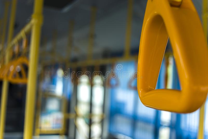 Punho de suspensão amarelo para passageiros de posição em um ônibus moderno Transporte suburbano e urbano foto de stock royalty free