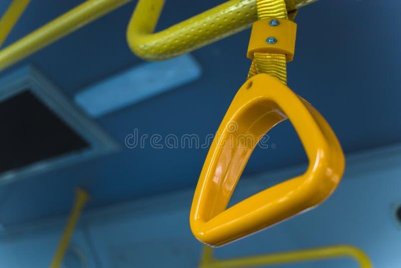 Punho de suspensão amarelo para passageiros de posição em um ônibus moderno Transporte suburbano e urbano fotos de stock royalty free