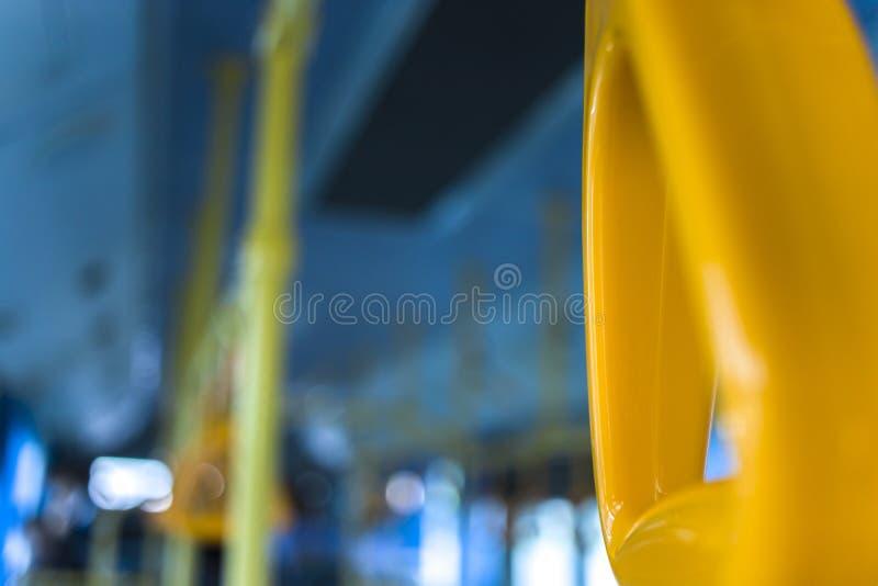Punho de suspensão amarelo para passageiros de posição em um ônibus moderno Transporte suburbano e urbano imagens de stock royalty free