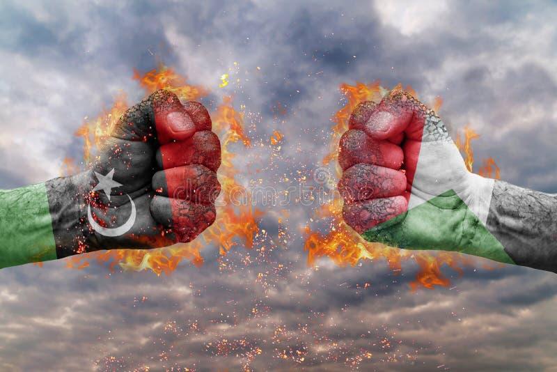 Punho dois com a bandeira de Líbia e de Sudão enfrentados em se imagens de stock royalty free