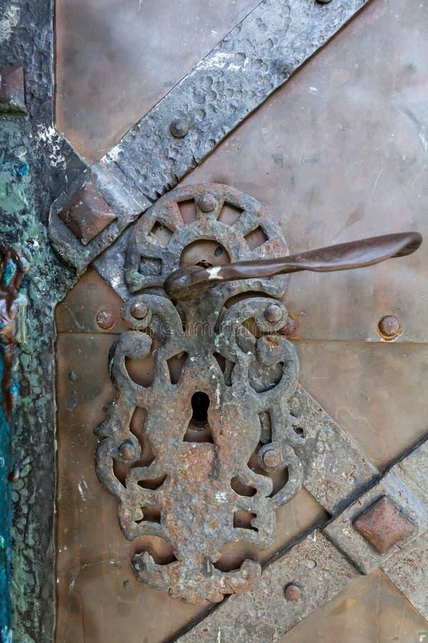 Punho forjado do metal na porta cinzenta escura do metal do vintage imagem de stock royalty free