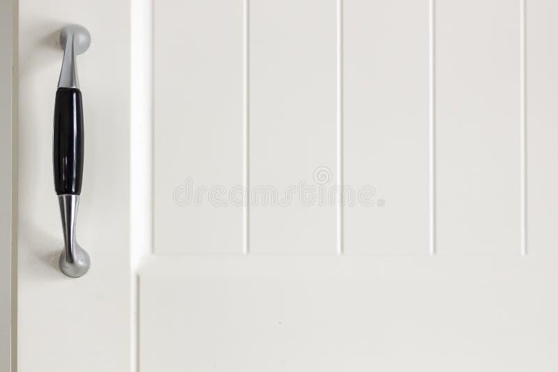 Punho na porta de armário pintada branca da cozinha na luz suave fotos de stock royalty free