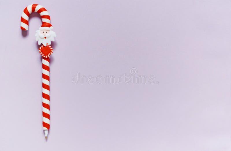Punho sob a forma de um bastão do caramelo do Natal em um fundo lilás espaço da cópia, letra a Santa Os doces do Feliz Natal pode imagem de stock