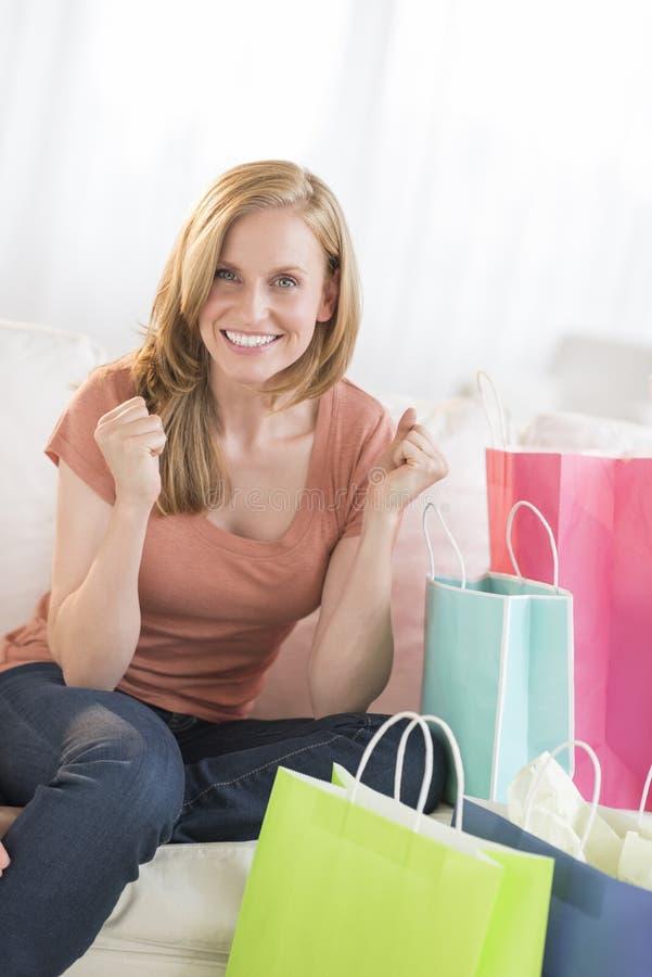 Punhos de aperto da mulher com os sacos de compras no sofá fotografia de stock
