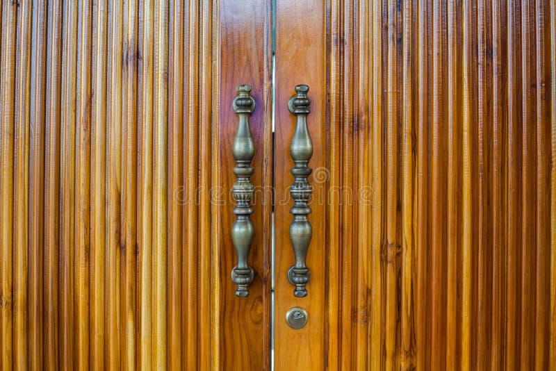 Punhos de bronze da porta de madeira fotografia de stock