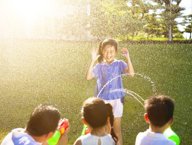 Punição da menina para que o pulverizador da arma de água molhe o corpo fotografia de stock royalty free