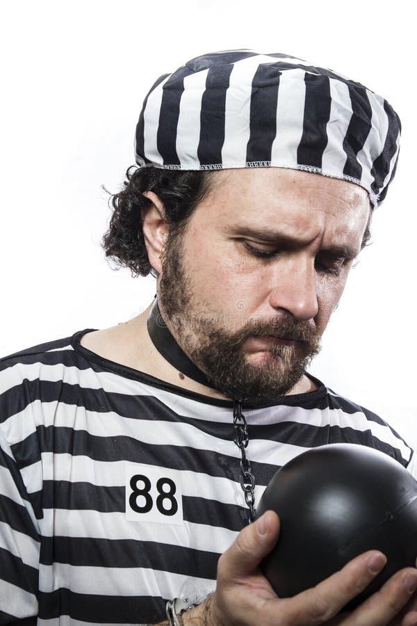 Punizione, un criminale caucasico del prigioniero dell'uomo con la palla a catena fotografia stock