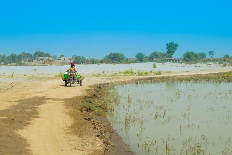Punjab, Paquistão-junho 23,2019: um homem não identificado que conduz um riquexó do moto em uma área afetada da inundação fotos de stock