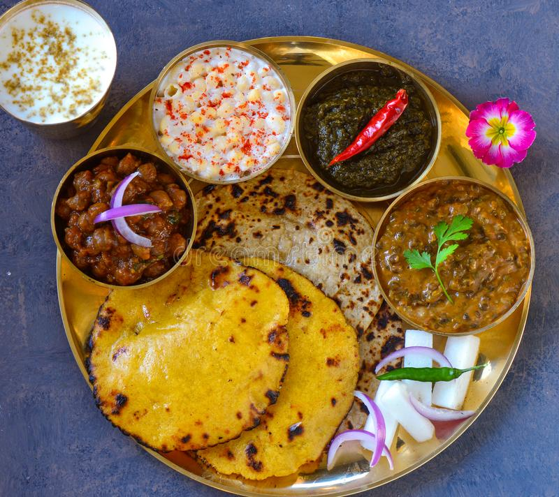 Punjabi vegetarian thaali meals served traditionally in brass plate stock photography