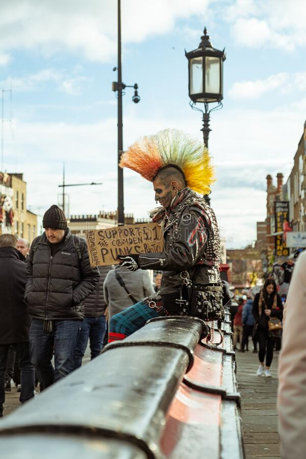 Punk in Camden Town, London. London / UK - Dec 01, 2019: tattoed face punk with colorful mohawk sitting on the street in Camden Town. The punk subculture emerged stock image