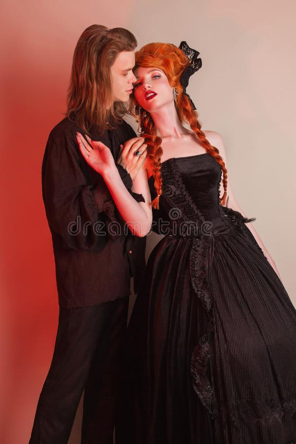 Punk couple in halloween clothes. Gothic costume for halloween party. Pale undead vampire in unusual carnival clothes. royalty free stock photography