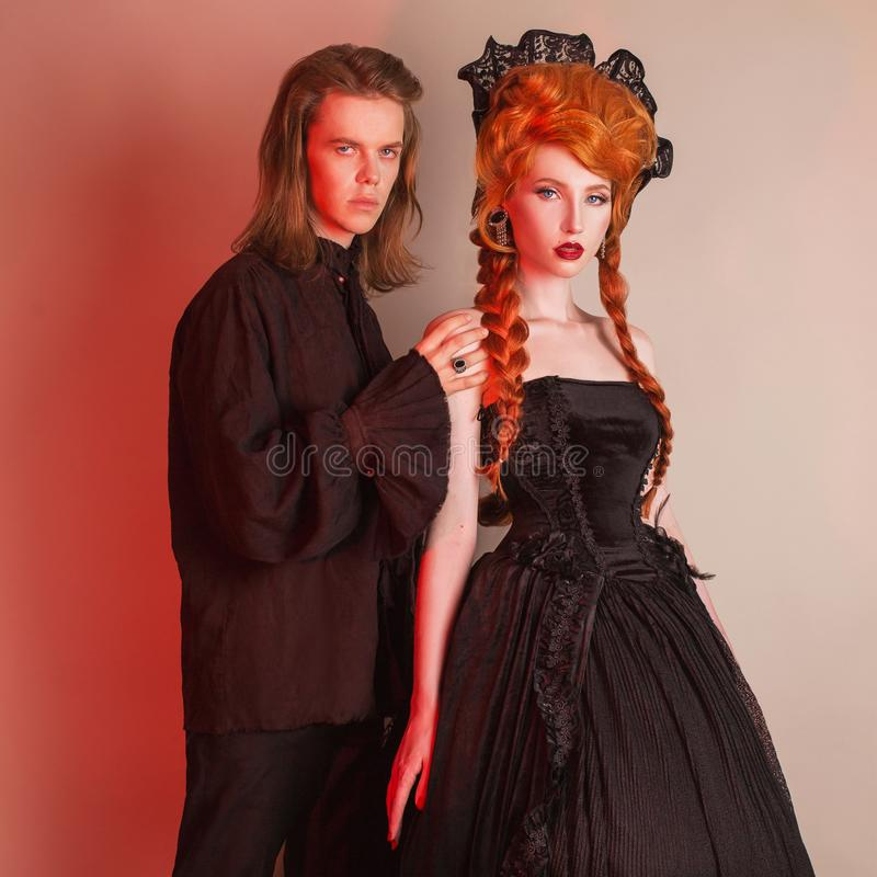 Punk couple in halloween costume. Pale undead vampire in edwardian carnival clothes. Gothic costume for halloween party. royalty free stock photos