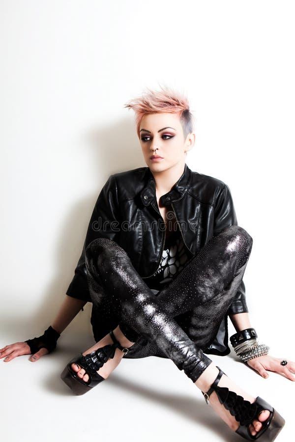 Punk fêmea novo que senta-se de encontro a uma parede fotografia de stock royalty free