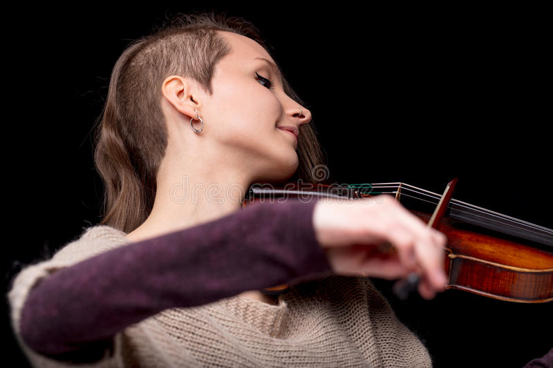 Punk folk violinist woman smiling and playing. Passionate punk classical music player is a violinist beautiful woman enjoying her professionalism and skill royalty free stock photos