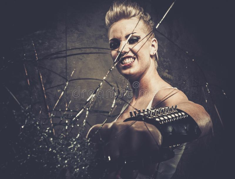 Punk girl behind broken glass stock photos