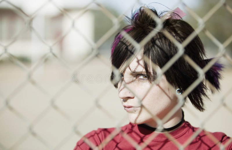 Punk Girl Behind Chain Link. Young Punk Girl Being Shadowed By Chain Link stock photography