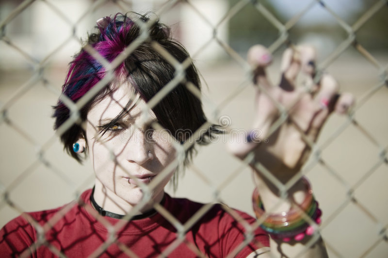 Punk Girl Behind Chain Link. Young Punk Girl Being Shadowed By Chain Link royalty free stock image