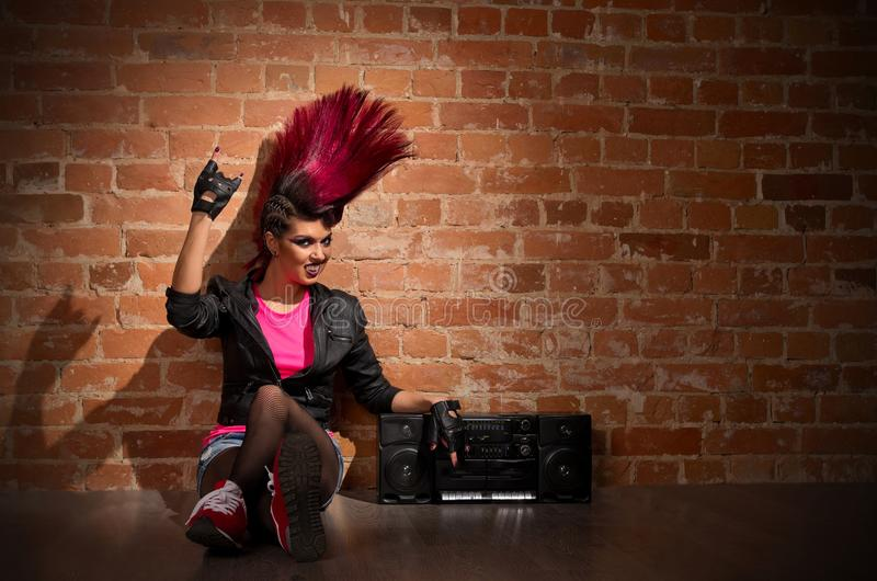 Punk girl on brick wall background royalty free stock photography