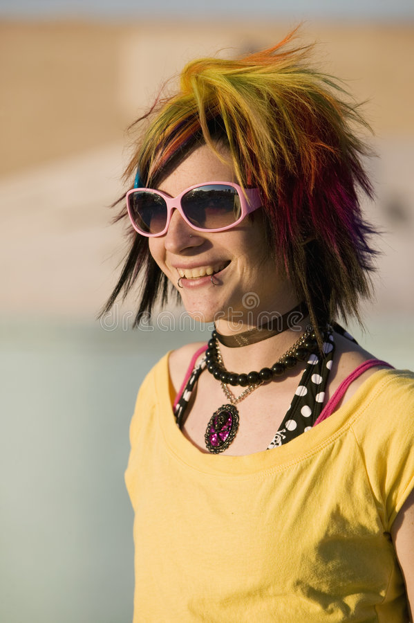 Punk Girl with Bright Colorful and Big Sunglasses. Portrait of a Smiling Punk Girl with Bright Colorful and Big Sunglasses Outdoors at Sundown stock photo