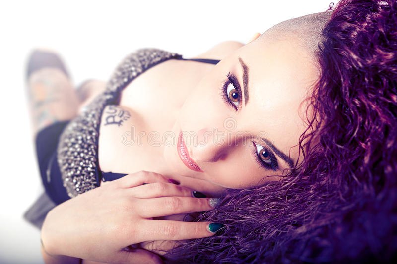 Punk girl, face makeup. Beauty and tattoo. Hair shaved on one side. A beautiful young woman is lying. Tattoos on her breast and leg. Concept of youthful beauty royalty free stock image
