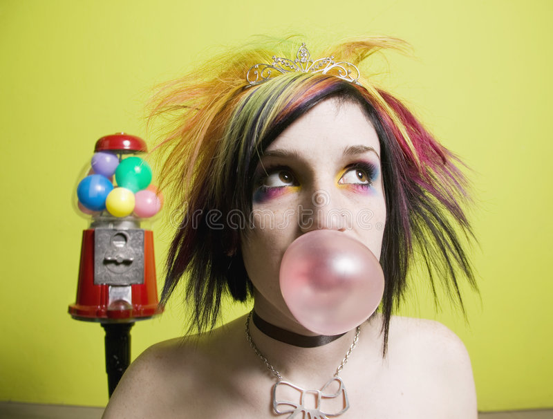 Punk Girl in front of a Green Wall. Blowing a Bubble royalty free stock image