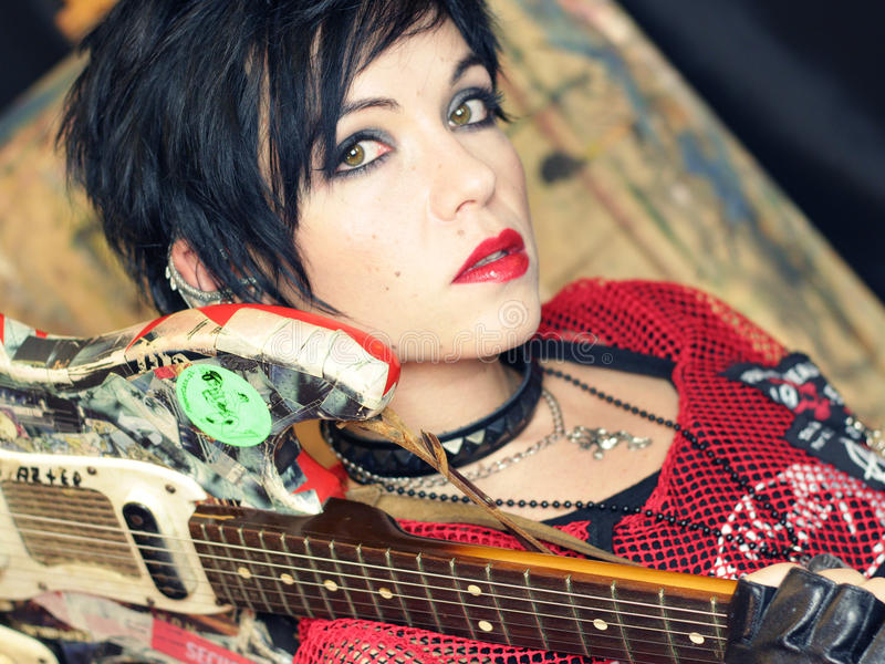 Punk girl with guitar. Portrait of black hair punk girl with guitar royalty free stock images