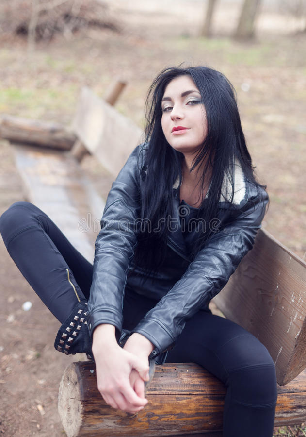 Punk girl. Sitting on the bench in the park and looking at camera royalty free stock images