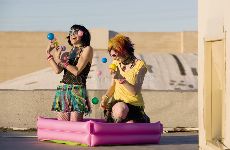 Punk Girls Juggling Plastic Balls. On a Rooftop royalty free stock photography