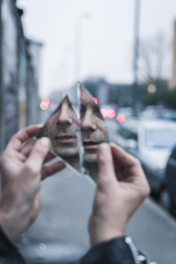Punk guy looking at himself in a shattered mirror stock images