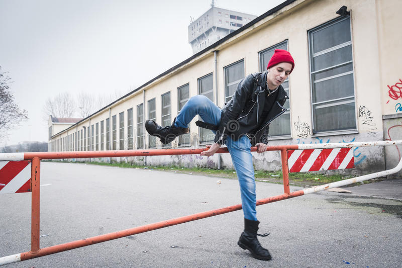 Punk guy posing in the city streets royalty free stock photo