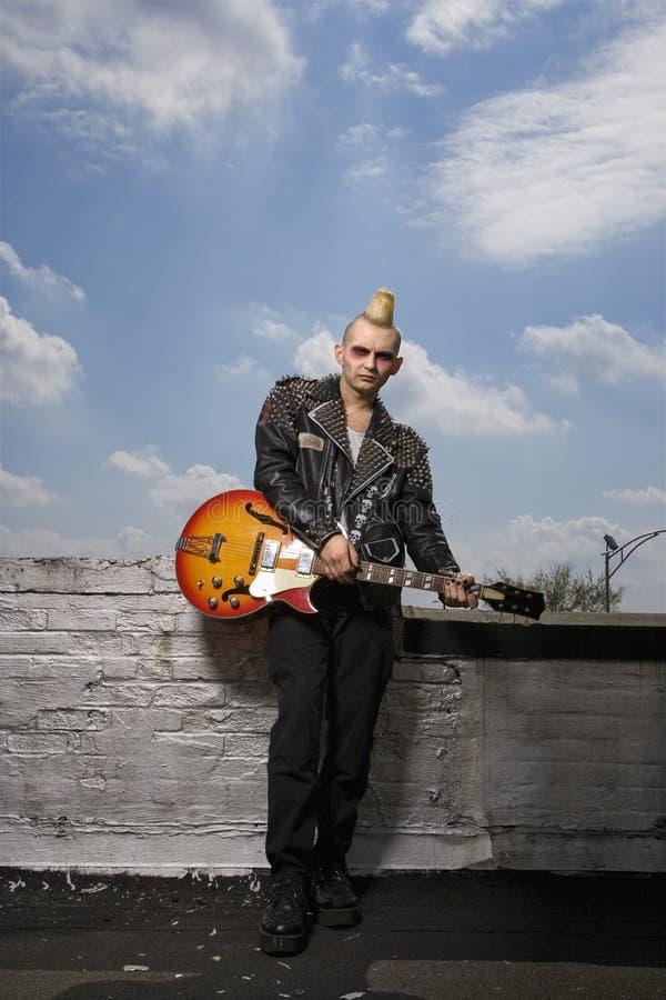 Punk holding guitar. royalty free stock photo