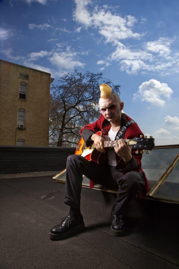 Punk playing guitar. stock photos
