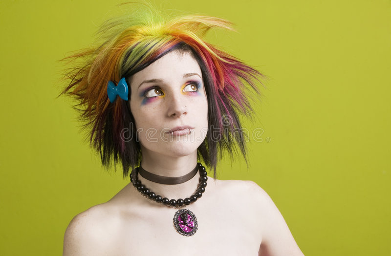Punk woman with bright makeup and bare shoulders. Close-up of a woman with bright mascara, colorful hair and bare shoulders stock images