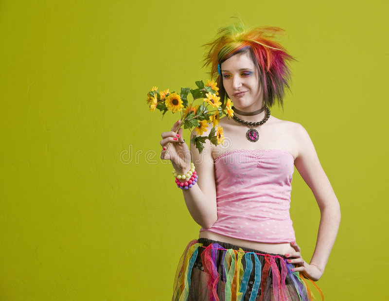 Punk woman with plastic flowers. Pretty young woman with colorful punk clothes considers plastic flowers stock images