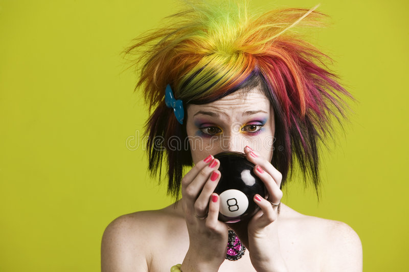 Punk woman with reading the future. Close-up of a woman with bright mascara and colorful hair predicts the future royalty free stock images