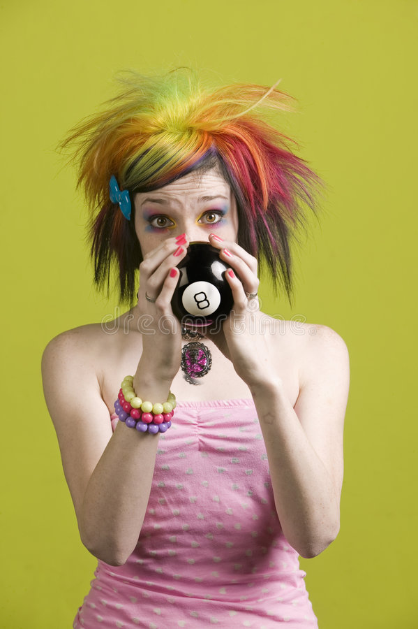 Punk woman with reading the future. Close-up of a woman with bright mascara and colorful hair predicts the future royalty free stock photo